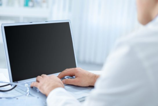 Mieslääkäri tietokoneella