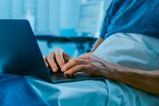 Potilas kirjoittaa kannettavalla tietokoneella sairaalasängyssä