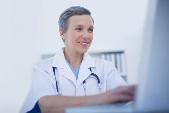 Hymyilevä naislääkäri tietokoneella
