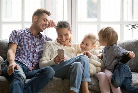 Nuori perhe kahden lapsen kanssa sohvalla