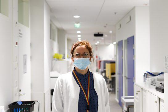 Sairaanhoitaja seisoo työvaatteissaan terveysaseman käytävllä