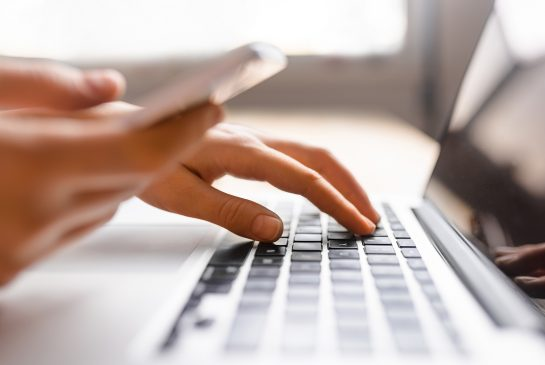 Kädet tietokoneen näppäimistöllä ja toisessa kädessä puhelin