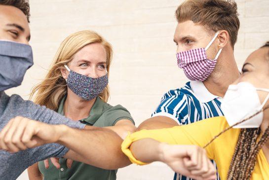 Iloiset nuoret tekevät koronatervehdyksen kyynärpäillä maskit päässä.