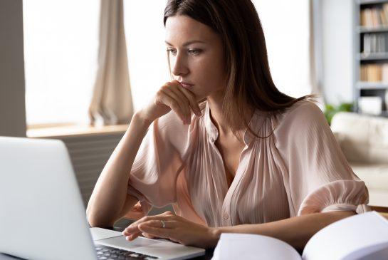 Nainen vakavannäköisenä tietokoneella, vieressä kirja auki