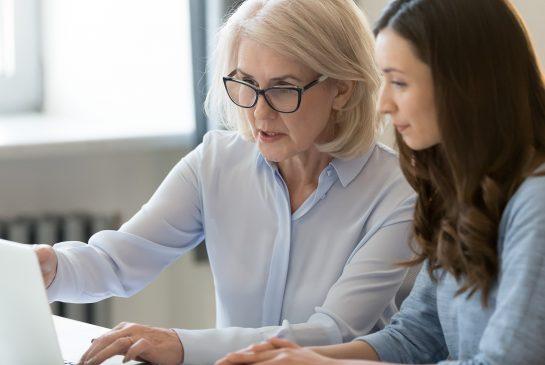 Kaksi naista istuu tietokoneen ääressä.
